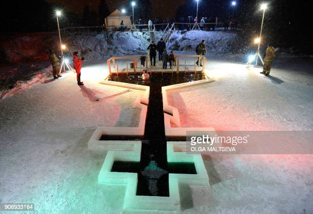 TOPSHOT Orthodox believers plunge into the icy waters of a pond during the celebration of the Epiphany holiday in the village of Tyarlevo outside...