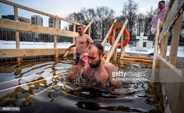 Orthodox believers plunge into the icy waters of a pond during the celebration of the Epiphany holiday in Moscow on January 19 2018 / AFP PHOTO /...