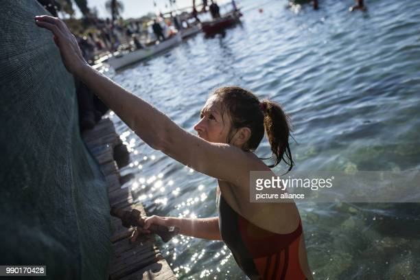 Orthodox believers try to retrieve a wooden crucifix during the annual Epiphany Day and the blessing of the waters celebrations in Piraeus near...