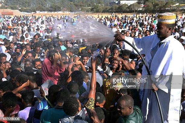 Orthodox Christian Ethiopians gathered at a field in Jan Meda are baptised with the holy water as part of the Epiphany celebrations in Addis Ababa...
