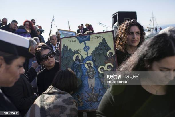 Orthodox Christian faithfuls carry a picture of the Lord during the annual Epiphany Day celebrations in Piraeus near Athens Greece 06 January 2018...