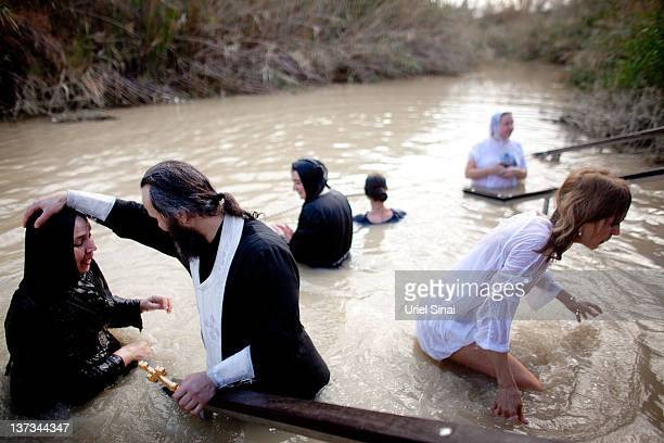 Orthodox Christian pilgrim is baptized during Epiphany celebrations in the Jordan River January 19 2012 at the Qasir alYahud baptismal site near...
