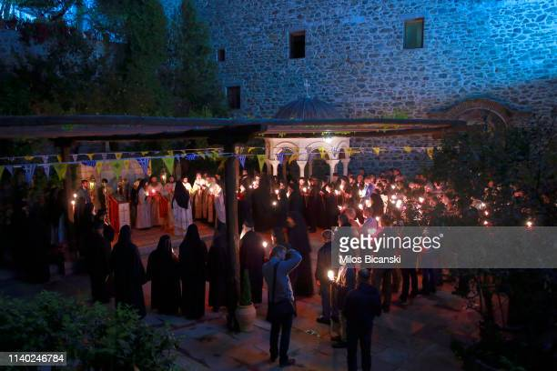 Orthodox Christian worshippers and Monks of the Osiou Gregoriou monastery hold a candles with the Holy flame during the early Easter Sunday Mass at...
