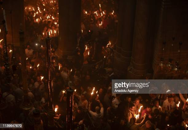 Orthodox Christian worshippers hold up candles lit from the Holy Fire as they gather at the Tomb of Christ as the miracle of the Holy Fire ceremony...