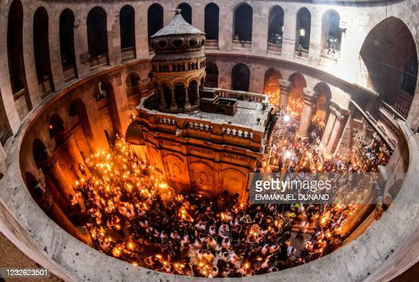 Orthodox Christians gather with lit candles around the Edicule, traditionally believed to be the burial site of Jesus Christ, during the Holy Fire...