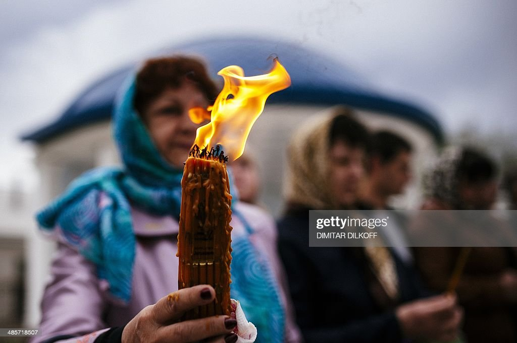 Orthodox Christians hold candles as they take part in Easter celebrations outside a church in the eastern Ukrainian city of Lugansk on April 20, 2014.