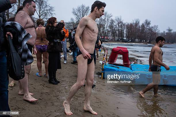 Orthodox Christians stand on the beach after bathing in the Dnieper River for Epiphany on January 19 2015 in Kiev Ukraine The holiday celebrates the...