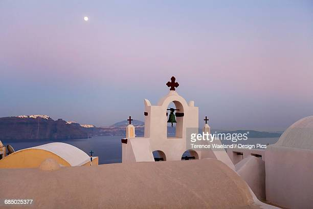 orthodox church with bell and a moon high in the sky at dusk - terence waeland stock pictures, royalty-free photos & images