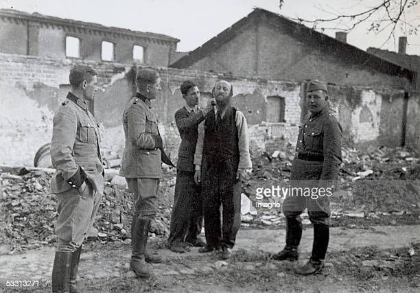 Orthodox Jew gets shaved off his beard by a civilian to humiliate him Three German soldiers are watching Zydom Photography 1939 [Holocaust Orthodoxem...