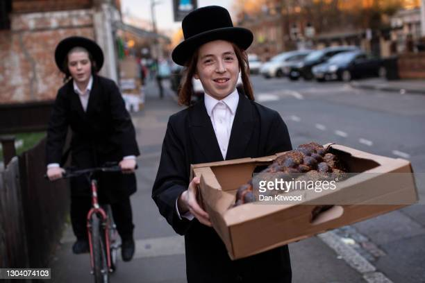 Orthodox Jewish children carry a box of bread ahead of Purim on February 25, 2021 in London, England. Last year's Purim occurred before the first...