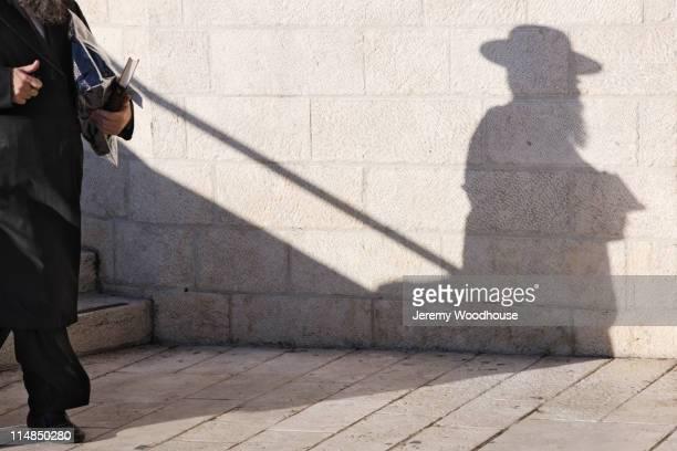 orthodox jewish man walking on sidewalk - jeremy woodhouse stock pictures, royalty-free photos & images