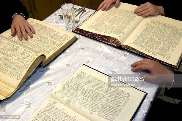 Orthodox Jewish men from the same Cohen family sit reading the Torah together at a table inside their Sukkah during the festival of Sukkot.