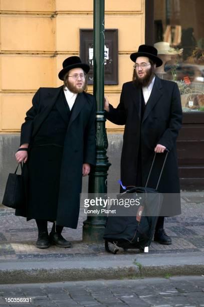Orthodox Jewish men leaning on lamp-post.