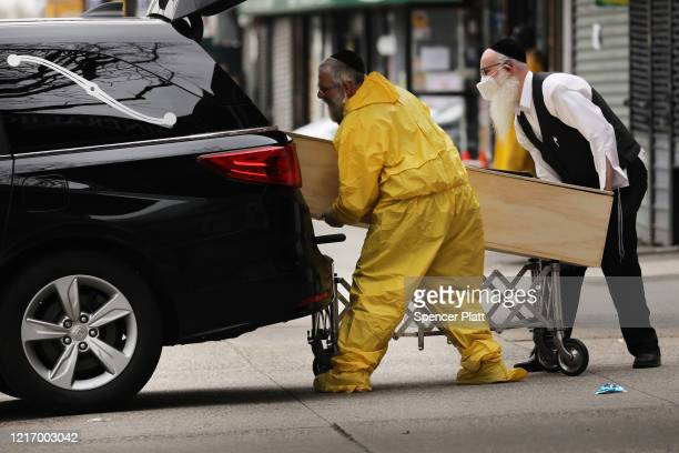 Orthodox Jewish men move a wooden casket from a hearse at a funeral home in the Borough Park neighborhood which has seen an upsurge of patients...