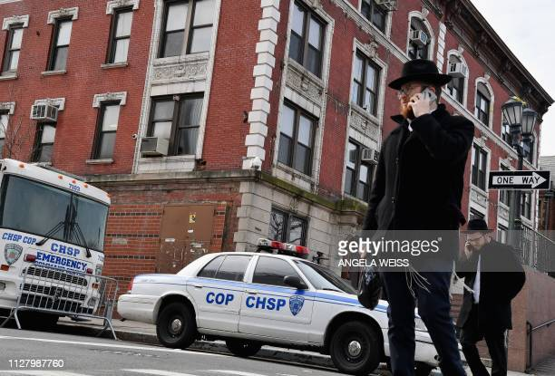 Orthodox Jewish men walk past a 'Crown Heights Shmira Patrol' security vehicles in the Brooklyn neighborhood of Crown Heights on February 27, 2019 in...