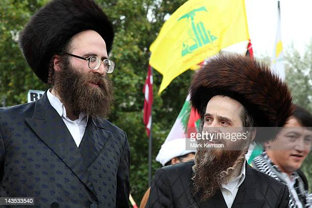 Orthodox Jews belonging to Neturei Karta prepare for the annual Al-Quds march London. A Hezbollah flag flies behind.