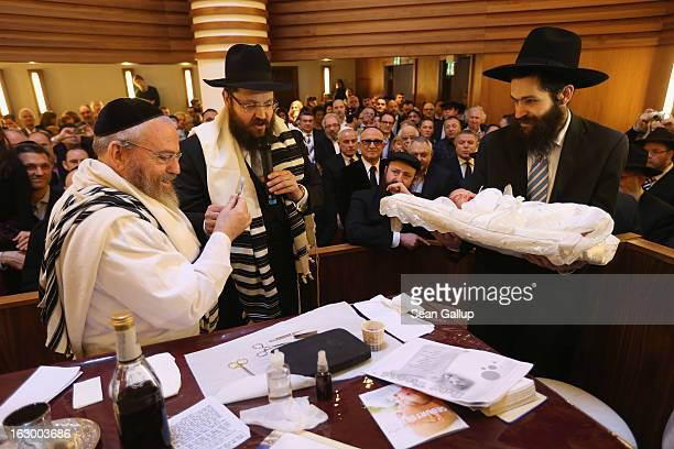 Orthodox Jews pass baby infant Mendl Teichtal to one another before his circumcision at the Chabad Lubawitsch Orthodox Jewish synagogue on March 3...