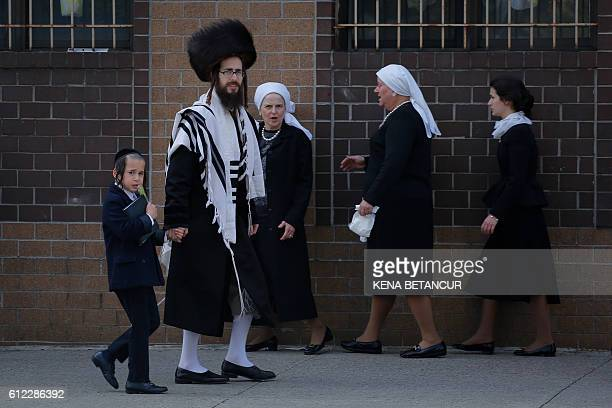 TOPSHOT Orthodox Jews walk to take part in the celebrations of Rosh Hashanah the Jewish New Year in Brooklyn New York on October 3 2016 / AFP / KENA...