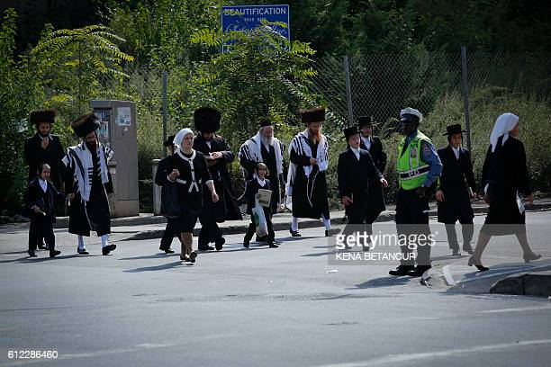 Orthodox Jews walk to take part in the celebrations of Rosh Hashanah the Jewish New Year in Brooklyn New York on October 3 2016 / AFP / KENA BETANCUR