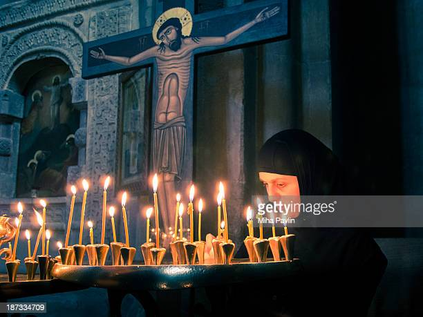 Orthodox nun lighting candles inside Svetitskhoveli cathedral, most venerated places of worship for Georgian Orthodox Christians, Mtskheta, Caucasus,...