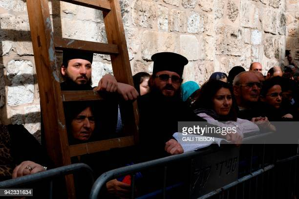 Orthodox pilgrims watch as Greek Orthodox Patriarch of Jerusalem Theophilos III conducts the traditional Washing of the Feet ceremony in front of the...