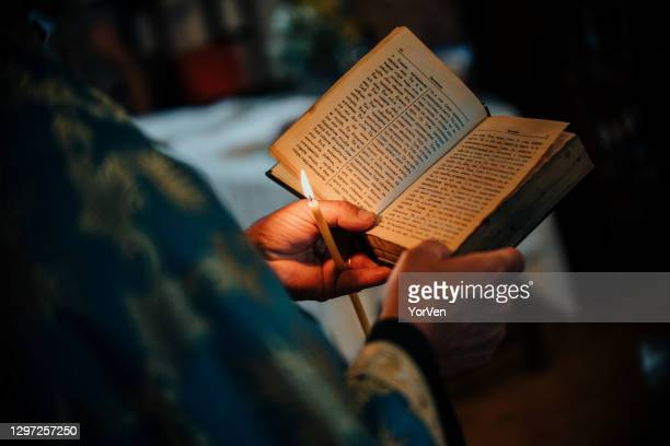 orthodox priest reading from the holy bible. - orthodox easter stock pictures, royalty-free photos & images