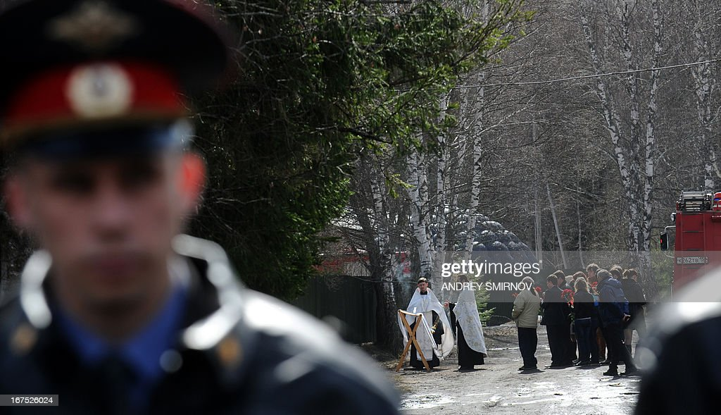 Orthodox priests conduct service in front of the burned psychiatric hospital in the small town of Ramensky around 40 kilometres (25 miles) outside Moscow, on April 26, 2013. Thirty-eight people, mostly psychiatric patients, were killed in a fire that raged today at a psychiatric hospital in the Moscow region, trapping the inmates inside behind barred windows.