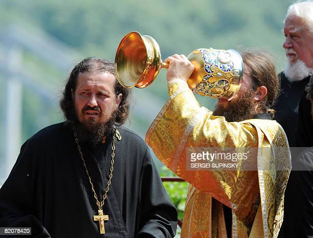 Orthodox priests drink altar wine after a liturgy on a treelined river bank in Kiev where Prince Vladimir the Great baptised his followers 1020 years...