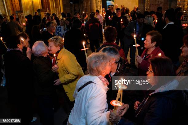 Orthodox worshippers kiss and greet each other celebrating Easter outside Faneromeni church in the old city of Nicosia after the postmidnight Easter...