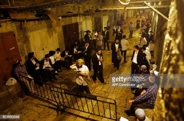 OrthodoxJews pray at a gate leading to the AlAqsa mosque compound in the Muslim quarter of Jerusalem's Old City on July 31 during the annual Tisha...