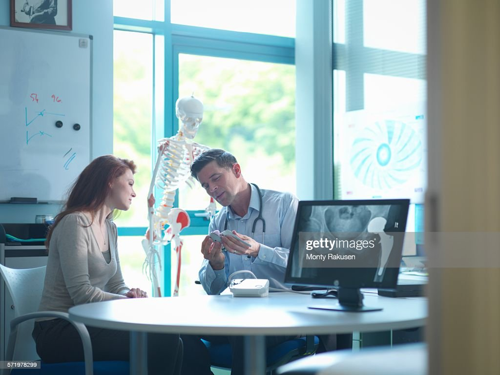 Orthopaedic consultant with patient in consulting room : Stock Photo