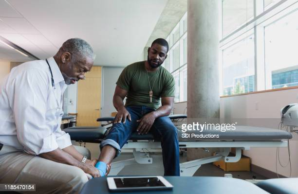 orthopedic doctor examines injured soldier's ankle - army physical exam stock pictures, royalty-free photos & images