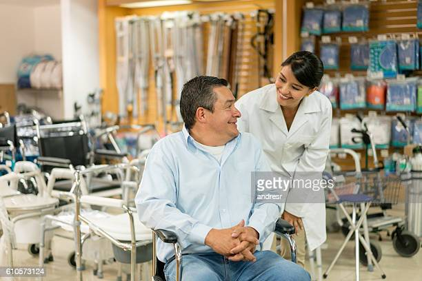 orthopedist helping disabled man - medical supplies stock pictures, royalty-free photos & images