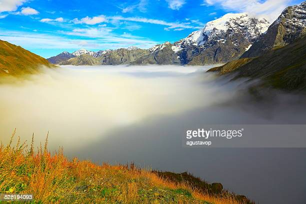 Ortler Stelvio Mountain pass above clouds blue sky, Italy