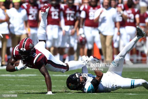 OrTre Smith of the South Carolina Gamecocks dives for extra yardage against Preston Carey of the Coastal Carolina Chanticleers at WilliamsBrice...