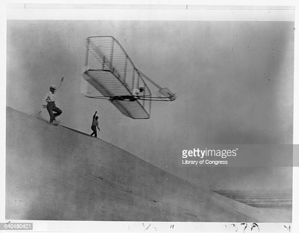 Orville Wright and Dan Tate launch the third Wright Glider into the air with Wilbur Wright aboard as pilot at Kill Devil Hill on October 18 1902 This...