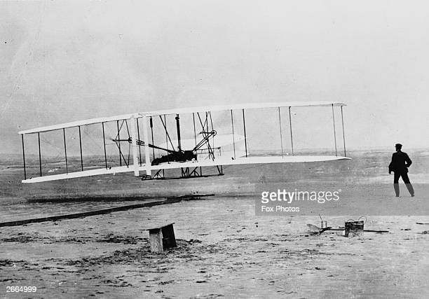 Orville Wright flying a Wright glider fitted with a Wright-designed 12hp engine at Kill Devil Hills, near Kitty Hawk, North Carolina. The flight was...