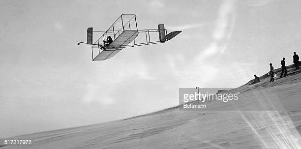 Orville Wright glides over Kitty Hawk in the Wrights' 1911 glider while others look on.