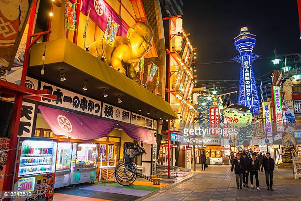 Osaka Billiken baby Tsutenkaku Tower overlooking neon lights Shinsekai Japan