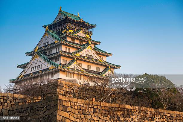 Osaka Castle illuminated by warm light of sunset Japan