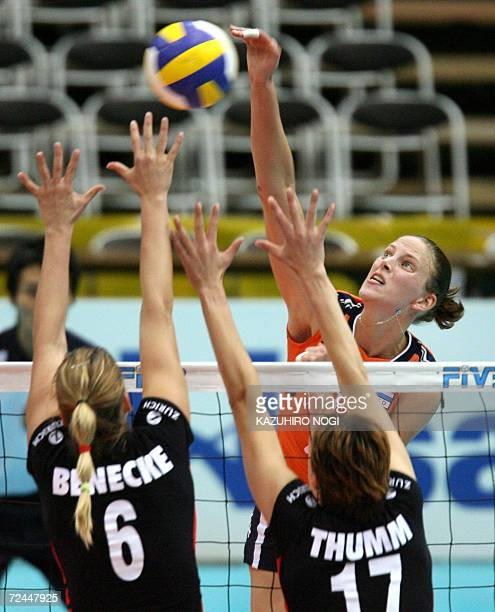 Dutch Chaine Staelens spikes a ball over German blockers Christina Benecke and Birgit Thumm during their pool F second round match of the women's...