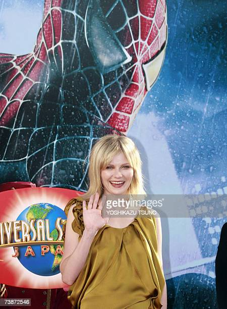 Hollywood actress Kirsten Dunst waves infront of a large picture of spiderman at a Hollywood theme park which has a 'Amazing Adventure of Spiderman'...