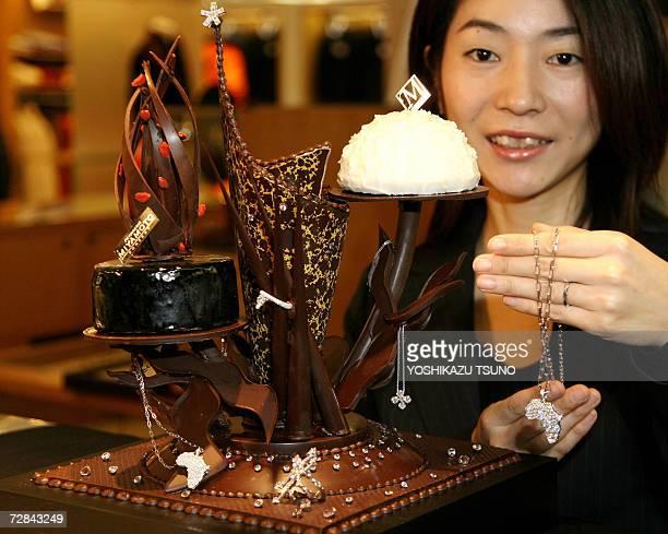 Japan's Takashimaya department store employee Noriko Wakiya displays the 100 million yen Christmas cake decorated with a total of 100 diamonds with a...