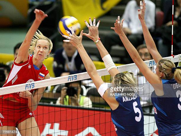 Russian attacker Elena Godina spikes the ball against Italian blockers Elisa Togut and Sara Anzanello during their semifinal match of the women's...