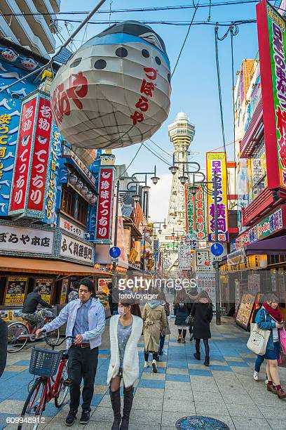 Osaka locals walking through colorful Shinsekai district Tsutenkaku Tower Japan