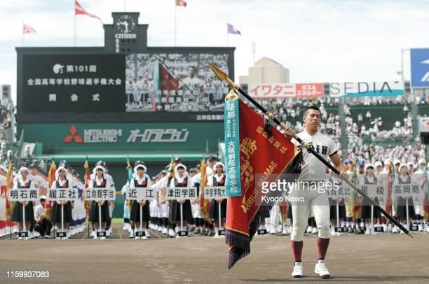 Osaka Toin captain Haru Nakano returns the championship flag during the opening ceremony of the national high school baseball tournament at Koshien...