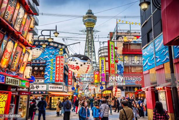 osaka tower en uitzicht op de neonreclames in het shinsekai district in de schemering, osaka, japan - japan stockfoto's en -beelden
