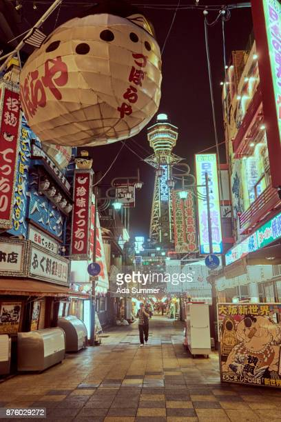 Osaka Tower and view of the neon advertisements Shinsekai district in a rainy night