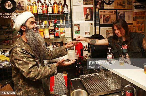 Osama bin Laden lookalike Ceara Francisco Helder Braga Fernandes receives payment in his 'Bar do Bin Laden' on April 29 2014 in Sao Paulo Brazil...