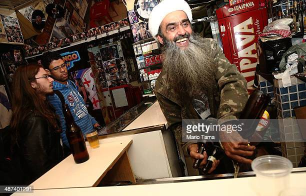 Osama bin Laden lookalike Ceara Francisco Helder Braga Fernandes serves customers in his 'Bar do Bin Laden' on April 29 2014 in Sao Paulo Brazil...